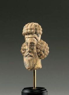 A PARTHIAN TERRACOTTA HEAD OF A MAN, CIRCA 1ST/2ND CENTURY A.D., of highly stylized form, his elongated face with striated palmette-shaped beard and wide moustache, the hair arranged in masses of circular curls on the crown and behind the nape of the neck; remains of pale blue glaze.