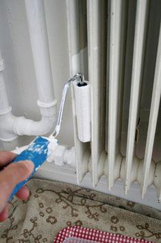 Chez Larsson paints a radiator.