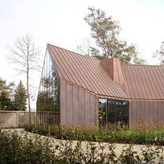 Untreated copper cladding will gradually change colour from golden brown to vivid turquoise on the walls and roof of this house near Ghent.