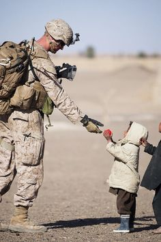 Soldier Giving Red Fruit on 2 Children during Daytime