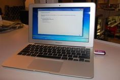 Windows 7 is being installed on a MacBook Air from a USB thumbdrive. Note: it's not necessary to use a pink drive.
