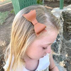 A beautiful cognac brown faux leather hair bow. Available on a soft nude nylon headband or hair clip.