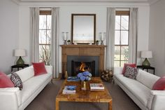 This Sagaponack living room has gray carpets, white couches with colorful pillows, an ornate fireplace, a mirror and vases on top of the fireplace and large windows.
