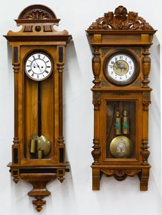 Lot 156: Mahogany Wall Clocks; Two items including a mahogany clock with painted grain wood insets, rounded crown, pendulum, weights and without key; and an oak carved clock with brass insets, pedulum, weights and key
