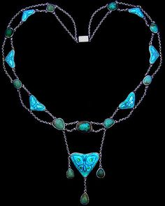 THE GUILD OF HANDICRAFT Ltd. (1888-1907) (Attributed) A silver Arts & Crafts butterfly necklace.  The double length chain has alternating enamel panels and collet set turquoise stones with a larger enamel to the centre. Each blue/green enamel of a butterfly is backed with sparkling silver foil. English. Circa 1900.