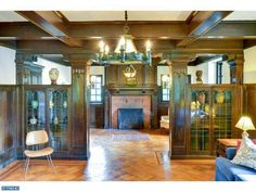Rooms with oak wainscoting, box beams, colonnade,   built-in cabinets with leaded glass cabinet doors, and original light fixtures – 1919 Arts & Crafts house (with Tudor/Gothic Revival touches), 6920 Boyer St, Philadelphia, PA