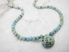 Stunning, faceted, ombre Amazonite rondelles with Indian Turquoise teardrop pendant accented with gold plated Hematite. ~ Amazonite Rondelles ~ Indian Turquoise Pendant 22.5 Strand 1 X 3/4 Indian Turquoise Pendant (approximately) ***This listing is for the LOVEY necklace only as shown