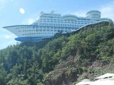 Sun Cruise Resort, Jeongdongjin, S. Korea designed as a cruise ship & built on a hill 50 m above sea level. 165 m long, 45 m tall. Astrogeo pos.:  latitude in creative, innovative air sign Aquarius sign of the sky, heaven, paradise, flying, abstraction, going new ways. Longitude between water sign Pisces sign of the ocean, imagination, dreaming, holidays & highly energetic fire sign Aries sign of action, ignition, aggression, speed, sports, The sharp pointed ship-bow is a typical for Aries…