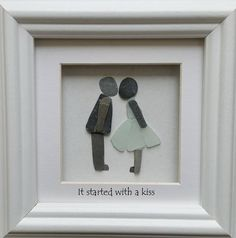 A little sea glass and stone couple sharing a kiss.  This piece is set inside a 20x20cm glazed box frame and is available in black or white, with or without the wording, or with wording of your own choice at no extra cost. Please leave a note with your preferences when you place your order.