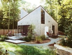 """Sited on a 12-acre lot, the structure peaks at 25 feet at its tallest points, providing spatial balance to its compact, 530-square-foot footprint. Large windows, a skylight, and a discrete chimney were all factors that contributed to its faceted form, which project architect Jack Ryan describes as a """"carved gemstone."""""""