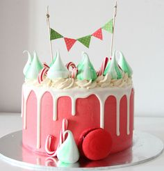 Christmas Drip CakeWhite glaze drip over red buttercream cake topper with peppermint candy cane and mint meringue cookies. (green and red bunting included/but packed separately)flavor: chocolate, vanilla or strawberry shortcakeprice: $65 / $100 size: serves 10-15pax / 20-25pax