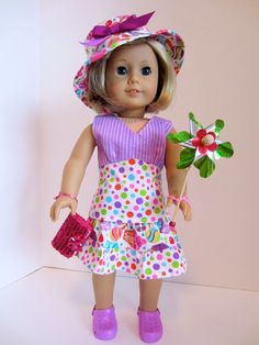 "Kit is wearing a lightweight plisse cotton outfit. It has a long halter top and a  three tiered skirt with repeating fabric of the top. The matching hat has a purple bow accent. She is carrying a pink ""purse"" and pinwheel, and wearing purple ""crocs."""