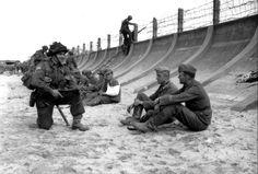 """Le Caporal Victor Deblois appartenant au peloton de Carriers du capitaine Michel Gauvin du Régiment de la Chaudière de la 3rd Cdn ID accroupi arme à la main devant deux prisonniers allemands assis au pied de la digue en béton à Juno Beach le D Day. D'autres prisonniers sont également assis le long de la digue en béton, dans le fond le Wn 28 """" La Cassine"""" de Bernières-sur-Mer. La garnison allemande de Bernières sur Mer appartient à la 5 Kp. du II/ Grenadier Regiment 736 de la 716 ID."""