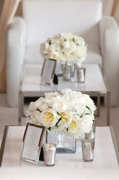 Mercury glass votive holders and white peonies in square glass vases decorate stylish low cocktail tables.