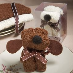 """Puppy Dog Towel - This cute puppy  is made of a towel/wash cloth that can have any number of good uses. This Favor is  made of a 100% cotton towel/wash cloth delicately folded and shaped.  Each measures 2.5"""" x 2"""" (towel is 7"""" square).  Shipped assorted,  two assorted """"breeds"""" of ivory and brown.  The puppy has a brown satin ribbon """"collar"""" with white stitched details, brown felt floppy ears and a black fuzy nose to complete the cutest canine you've ever seen"""