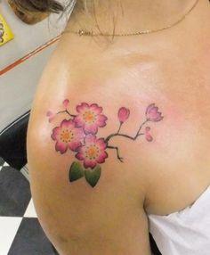 Petit tattoo fleur de cerisier sur l'épaule