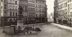 Paris, la place Dauphine photographiée (détail) par Charles Marville vers 1865, avec vue sur la statue d'Henri IV sur le Pont-Neuf. On découvre aussi la statue ou fontaine Desaix, disparue en 1874 en même temps que le côté de la place qui donne sur la rue de Harlay et le palais de Justice.