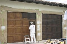Faux finish those metal garage doors. Add some hardware, and voila you've got expensive carriage doors.