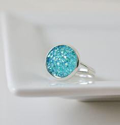 This beautiful druzy ring was made using a blue faux druzy resin cabochon that has a shimmer just like a real druzy. It is attached to an adjustable silver ring. All of our rings come in a cotton line