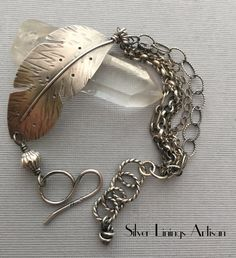 I have designed and hand cut from sterling silver sheet a large feather, connected to sterling links and five assorted sterling silver chains. I have carefully wire wrapped a handmade sterling silver Bali bead to my textured clasp. A handmade sterling silver tassel charm swings freely from one side and at the end. The bracelet has been oxidized to enhance the texture and hand polished. The sterling feather is approximately 2 inches in length and 3/4 inch across and is slightly curved to...