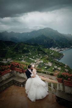 bride and groom embracing on a balcony that overlooks Italian landscape - photo by JoAnne Dunn via junebugweddings.com