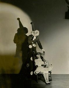 Evil smiling clown watches over his kidnap victim