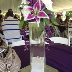 Centerpiece. Tall glass vase from dollar tree with sand filled half way. Two little fake wedding rings on top of sand then top it with fake dollar tree flowers
