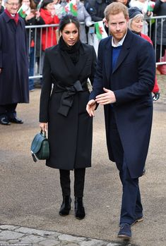 Meghan wrapped up against the biting cold in a black coat by Stella McCartney and trousers by the Welsh fashion house, Hiut Denim