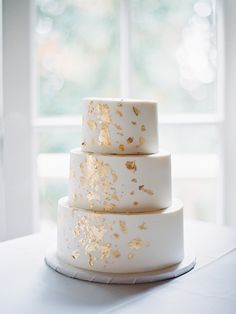 If you're the type of bride looking for just a little extra sparkle on your big day, then look no further than this elegant confection by James Xiong. Cascading gold foil flakes give this three-tiered white cake just a little something extra.