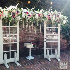 Vintage French door arch with five clusters of flowers, orchids, roses, cushion mums and iris for wedding ceremony backdrop at Firehouse Restaurant in Old Sac. Middle table with wine box for wine ceremony and butterflies for children to release