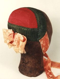 Frauenhaube, klein, von rotem Seidenstoff; mit grünem Bandbesatz, rosafarbener Bandschleife und rosa Bindebändern. Die Haube stammt vom Festland-Nordfriesland. #NordFriesland