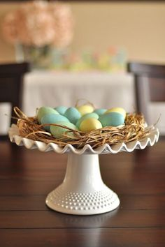 Cake Stand Nest Using wooden eggs and brush from her front yard, this blogger assembled a little Easter nest atop a cake stand and it's almost too cute for words. Get more stylish Easter DIYs at HouseBeautiful.com.