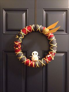 Harry Potter Wreath // I say: I didn't end up making one like this for the party decor, but I did use this idea and have made a Hogwarts yarn wreath featuring the house colors. I like the crisscrossing accents, which are simple to do but really make the wreath look nicer.