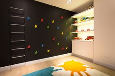 The contemporary kids room incorporates engaging furnishing ideas to keep the children entertained. An indoor climbing wall has been built onto a background of chalkboard paint with bespoke white shelving hosting a variety of toys and additional storage. The multi-coloured rug accomplishes the fun-filled look. #childrensplayare #childrensroom #wallclimbing #toys #bookshelves #carpet #rug