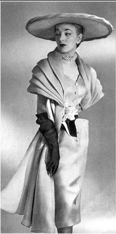 1951 Model in a grey organza pleated stole-mantle worn over dress of same fabric, waist is belted by yellow and black ribbon, by Robert Piguet