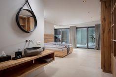 Schlafzimmer mit grauem Fliesenboden und Holz, ein Traumzimmer in einem edlen Design Apartment in den Kitzbüheler Alpen. Das Badezimmer ist direkt hinter