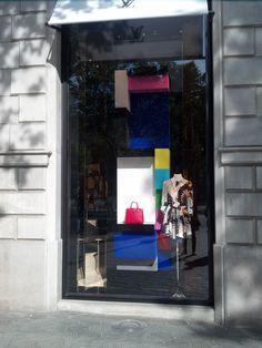 LOUIS VUITTON; en Paseo de Gracia nº80, Barcelona; Presenta un expositor colorido por la estación actual, y geométrico que recuerda a las obras de Piet Mondrian, cuyo artista fue uno de los referentes por parte de la marca; Los productos expuestos son: un bolso con un fondo blanco para contrastar, y a su lado derecho un maniquí con un vestido muy diferente comparado con los elementos de su alrededor; La composición del escaparate es vertical por el estrecho pero alto espacio.