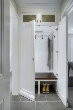 Fantastic concealed mudroom hidden behind closet doors with slate tiled floors alongside white doors opening up to reveal a built-in bench with coat hooks and grille front cabinets above Mudroom Cabinets, Mudroom Laundry Room, Closet Mudroom, Mudroom Cubbies, Entry Closet, Hall Closet, Entry Hall, Cabinet Doors, Utility Room Designs