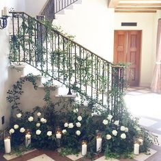 A dreamy staircase design with lush greenery, white garden roses and candles. A…