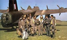 """Crew beside Stirling bomber. By December 1943 Stirlings were being withdrawn from frontline service as bombers, increasingly being used for minelaying outside German ports (""""Gardening"""" missions), electronic countermeasures and dropping spies deep behind enemy lines at night (through the unused ventral turret ring)."""