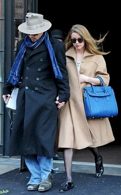 Amber Heard, with stylish round sunnies and a blue statement bag on hand, stayed close to fiancé Johnny Depp as the duo made their way through NYC.