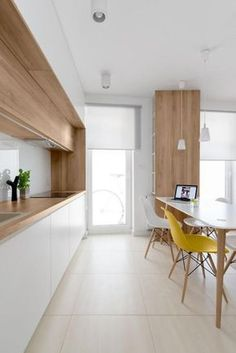 cuisine blanche plan de travail bois, table en bois et blanc et une chaise jaune