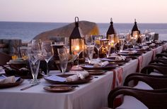 Beach table setting with lanterns overlooking water