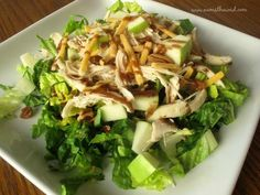 A salad with romaine lettuce, chicken, pecans, green apples, sharp cheddar cheese, and topped with a balsamic vinaigrette.