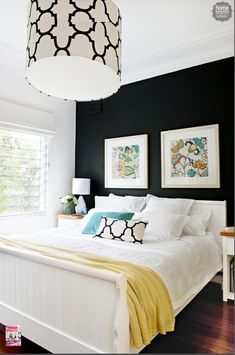 The contrast of the black wall and the light and bright bedding and decor makes a dramatic statement