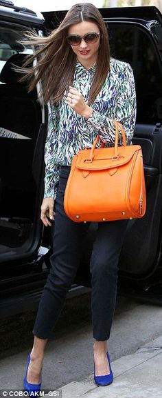 Miranda Kerr's sophisticated and fun: a print blouse, navy trousers, royal blue pumps and bright orange Alexander McQueen Heroine tote. #celebrity #streetstyle