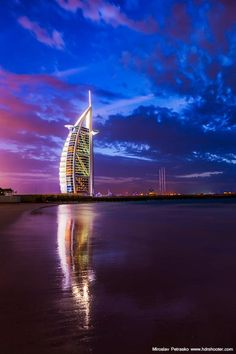 Known for its jaw-dropping architecture and engineering, Burj Al Arab is one of the most famous landmarks in Dubai. Shaped to resemble the sail of a ship, it's unique design has made it famous all over the world. Honeymoon In Dubai, Honeymoon Spots, Romantic Honeymoon, Burj Al Arab, Sharjah, Brunei, Abu Dhabi, Maldives, Places To Travel