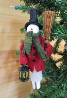 A more detailed version of our clothespin snowman, this Snowman wears a 3/4 length wool felt coat with black buttons. He carries a lantern with painted wooden candle inside in one hand and a straw broom in the other. Candles are randomly painted either red or white (white is shown in photo example). Lanterns are either round, as shown, or square.  You may select the color of his coat (red, dark blue, or green) or choose No Preference for a random selection. Please allow 1-3 business days...