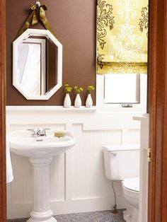 Simple Powder Room-Warm chocolate brown balanced with cream wainscoting and crisp white fixtures make this powder room feel welcoming and spacious. A classic Roman shade, clean-line molding, and a pretty pedestal sink add decoration without overwhelming the small space.
