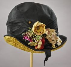 1920s black silk and straw silk cloche hat adorned with flowers.